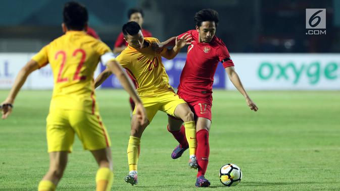 Pemain depan Timnas Indonesia U-19. Hanis Saghara Putra (kanan) mencoba melewati pemain China U-19, Qianglong Tao pada PSSI 88th U-19 International Tournament di Stadion Pakansari, Cibinong, (25/9). Indonesia kalah 0-3. (Googleberita.com/Helmi Fithriansyah)