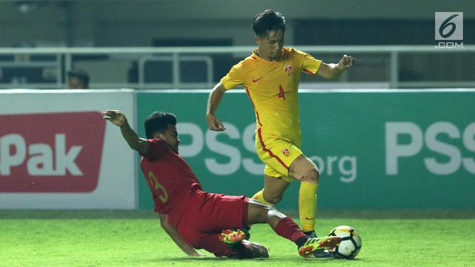 Bek Timnas Indonesia U-19, Asnawi Mangkualam (kiri) berusaha menahan pemain China U-19, Junwei Yu pada laga PSSI 88th U-19 International Tournament di Stadion Pakansari, Cibinong, Selasa (25/9). Indonesia kalah 0-3. (Googleberita.com/Helmi Fithriansyah)