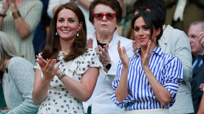 Duchess of Cambridge Kate Middleton dan Duchess of Sussex Meghan Markle bertepuk tangan saat menyaksikan pertandingan Serena Williams dan Angelique Kerber di kejuaraan  tenis Wimbledon di London, Inggris, (14/7). (AP Photo/Andrew Couldridge)