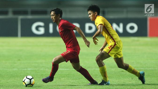 Pemain depan Timnas Indonesia U-19. Hanis Saghara Putra (kiri) mencoba melewati pemain China U-19, Ao Chen pada PSSI 88th U-19 International Tournament di Stadion Pakansari, Selasa (25/9). Indonesia kalah 0-3. (Googleberita.com/Helmi Fithriansyah)